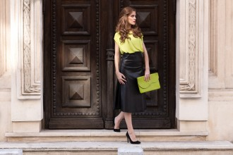 City chic young woman whearing a neon blouse and black leather skirt on beautiful city streets