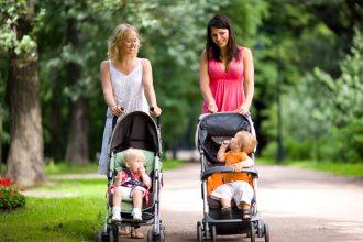 To unge kvinder går tur i skoven med deres børn i klapvogne