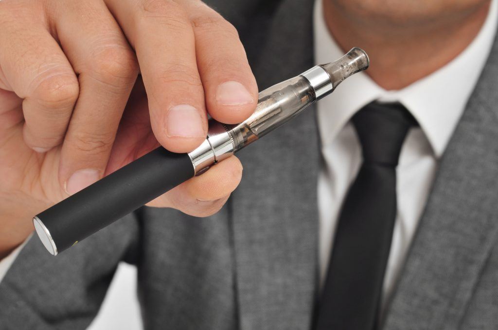 Mand i jakkesæt holder en elektronisk cigaret