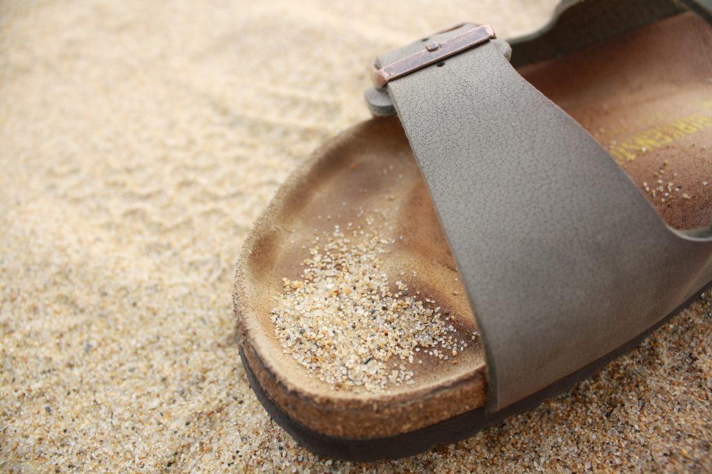 Sandal i læder med spænde og kork sål står på en baggrund af sand