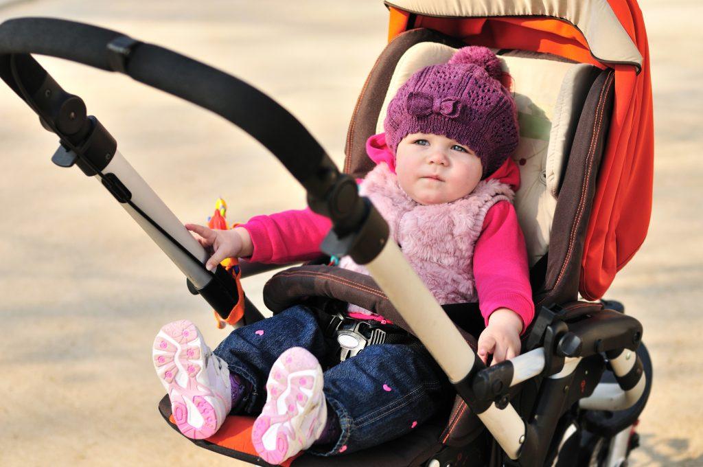 Baby iklædt varmt tøj i omvendt klapvogn