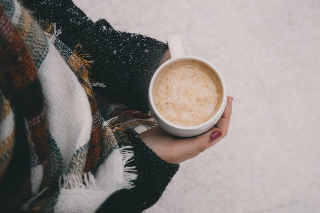 Dame i moderne tøj drikker kaffe