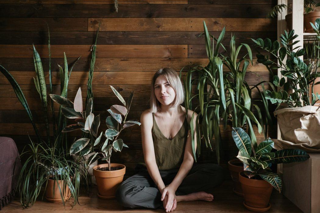 Dame sidder op ad trævæg med planter