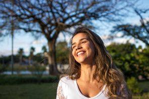 Kvinde står i naturen og smiler