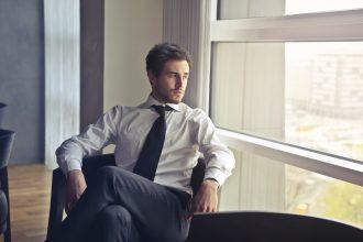 Mand kigger ud af vinduet med sort slips