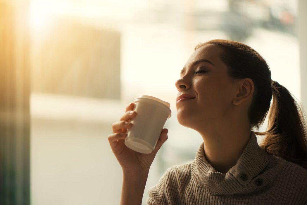 Ung dame drikker te i solen