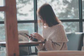 Kvinde bruger telefon på cafe