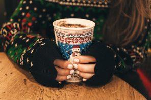 Kvinde holder varm kop med juletrøje på