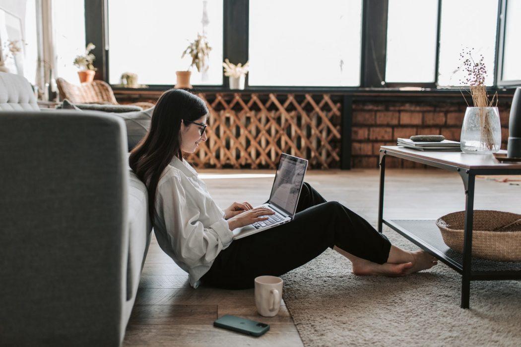 Dame sidder på gulv med sin bærbar computer